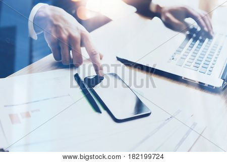 Man working on modern mobile phone and laptop at sunny office and pointing finger to home button of smartphone.Horizontal, blurred background, visual effects