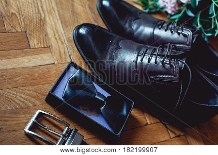 Close up of modern man accessories. Black bowtie, leather shoes, belt and wedding bouquet on wood rustic background. Set for formal style of wearing.