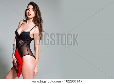 Sexy Woman With Red Lips In Black Bodysuit With Pillow