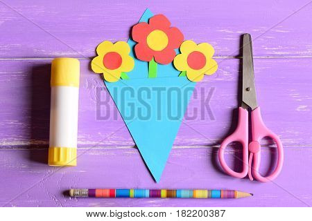 Making paper crafts for mother's day or birthday. Step. Paper flowers bouquet, scissors, glue stick, pencil on a wooden table. Set for kids creativity at home or in kindergarten. Top view