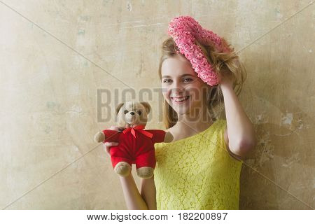 Pretty girl or cute smiling woman with blond hair and adorable happy face in yellow dress with teddy bear toy and pink wicker heart for valentines day on textured wall background copy space