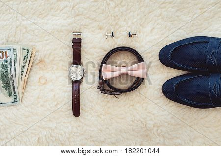 Close up of modern man accessories. Biege bowtie, leather shoes, belt, watch, cufflinks, money and wedding rings. formal style of wearing. look from above