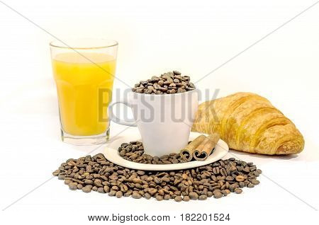 Cup of coffee filed with coffee beans with croissants, two cinnamon stick and orange juice on white background