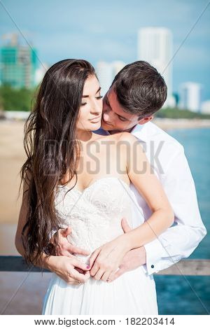 Newly married couple after wedding in luxury resort. Romantic bride and groom relaxing near swimming pool. Honeymoon. Tropical country.