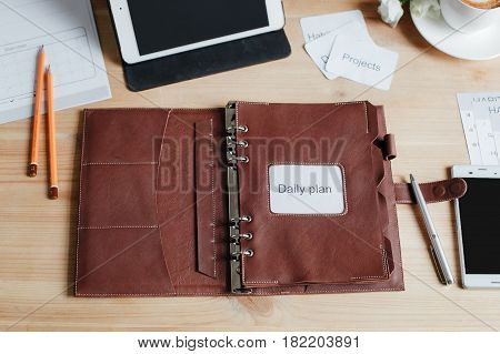 Notepad For Planning, Two Pencils, A Pen, A Smartphone, A Touch Pad On A Wooden Table. View From Abo