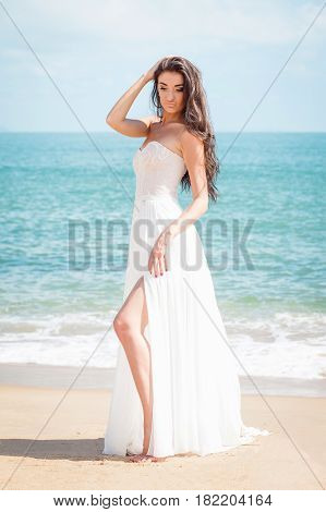 Bride walking down the beach in a white dress. Beautiful girl walks barefoot down the beach. Wedding day. Romantic atmosphere in tropical country. Caucasian model with long brown hair.
