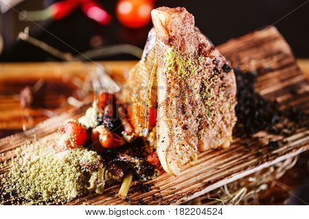 baked seabass and potatoes in a baking dish with spices on an wooden background. slice caramelized. selective focus.