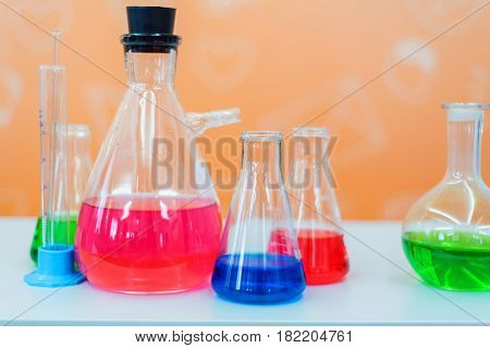 Laboratory expreriment with test-tubes with colored chemical reagents, retorts and flasks