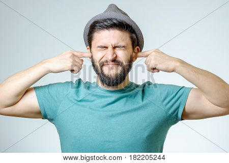 Annoyed Young Man Plugging Ears With Hands