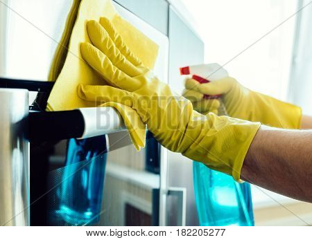 Man's Hand In Glove With Rag Cleaning Oven