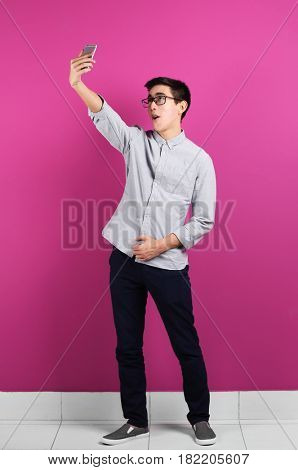Young Asian man taking selfie near color wall