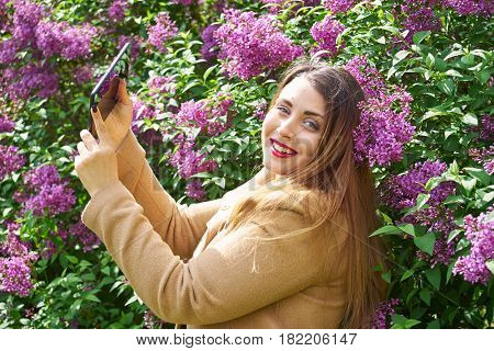Young beautiful woman in a beige coat making a selfie in front of lilac bush and looking at viewer.