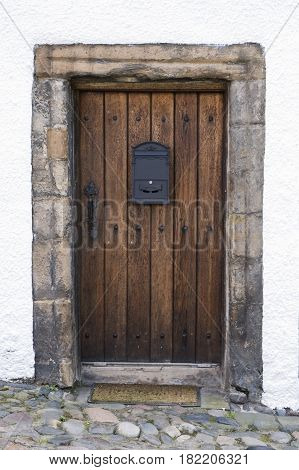 An image of an old oak door dating from the 1600's with black door furniture and cobbled entrance