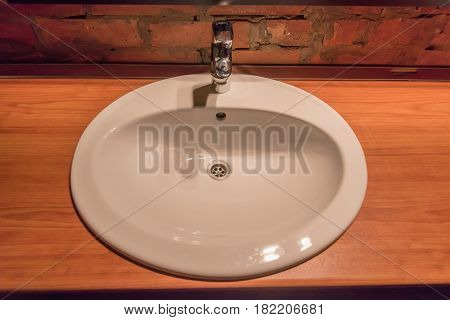 Close-up of ceramic or porcelain drain of kitchen sink with strain on wooden surface
