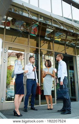 Group of young successful business people discussing work outside modern office building