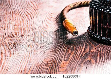 Hookah mouthpiece on textured mahogany wood surface. Close-up view