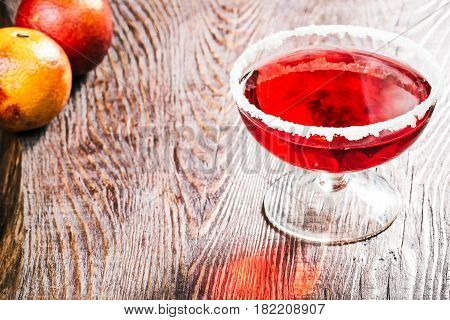 Glass of pomegranate juice with sugar border. Blood oranges on wood table. Close-up view