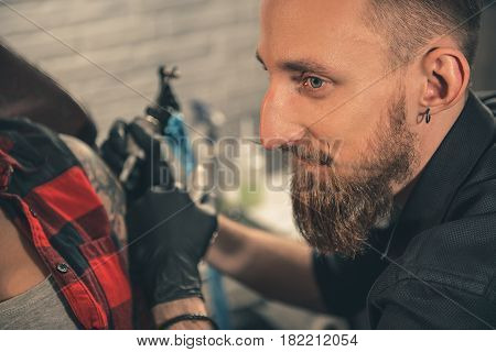 Focus on side view portrait of man expressing thoughtfulness while doing tattoo on hand of woman. Muse concept