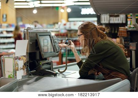 Side view image of confused cashier on workspace in supermarket shop. Looking aside.