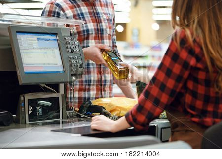 Cropped picture of young man standing near cashier's desk in supermarket.