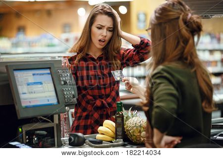 Photo of confused young lady standing in supermarket shop near cashier holding credit card.