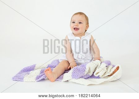 Photo of happy little baby girl sitting on floor with plaid isolated over white background. Looking aside.