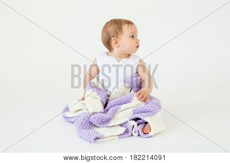 Picture of pretty little baby girl sitting on floor with plaid isolated over white background. Looking aside.