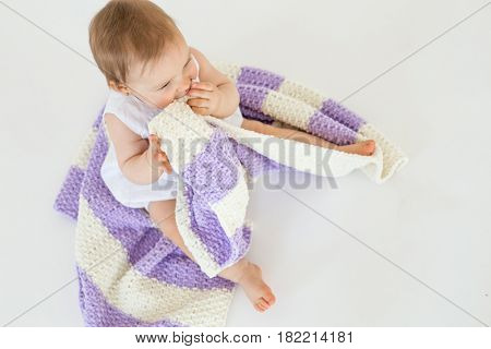 Top view photo of pretty little baby girl sitting on floor with plaid isolated over white background. Looking aside.