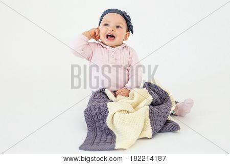 Photo of cheerful girl sitting on floor with plaid isolated over white background. Looking aside.