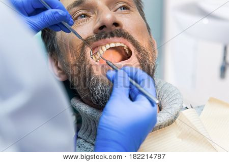 Adult person at the dentist. Doctor is checking teeth. Free dental diagnostics.
