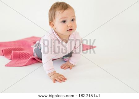 Photo of cute pretty baby girl sitting on floor with plaid isolated over white background. Looking aside.