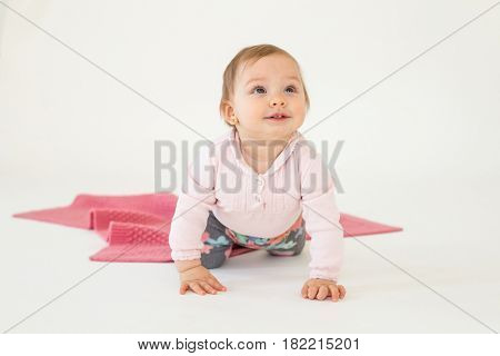 Picture of pretty cute baby girl sitting on floor isolated over white background. Looking aside.