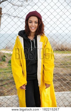 Photo of cheerful african young lady walking outdoors dressed in yellow raincoat. Looking at camera.