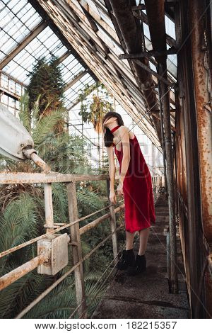 Attractive young woman in red dress facing obstacles at greenhouse