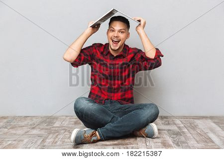 Portrait of a cheerful young man in plaid shirt holding laptop over head while sitting on the floor isolated over gray background