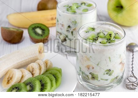 Yogurt with banana and kiwi slices and a plate with sliced fruit on a wooden table.