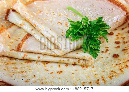 Pancakes with sour cream in a bowl on a wooden background.