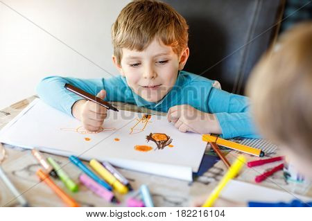 Two little kids boys at home making homework, painting a story with colorful pens. Little children writing with pencils, indoors. Elementary school and education, imagine fantasy concept.