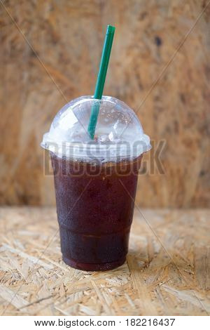 Plastic cup of iced black coffee americano on wooden table in a coffee shop