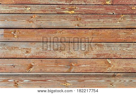 Fragment of peeled brown painted wooden boards background