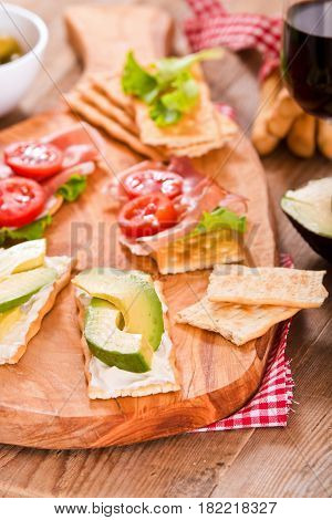 Crackers with ham and avocado on cuttingboard.