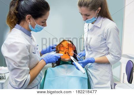 Dental doctor using curing light. Woman at dentist office. Effective methods of teeth treatment.