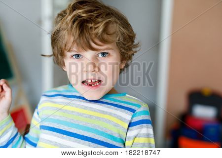 Portrait of little cute school kid boy colorful school uniform fashion clothes. Child with tooth gap smiling and looking at the camera. Happy blond boy