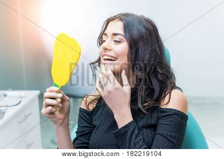 Woman looking at her teeth. Smiling lady at dentist office. Smile as a masterpiece.
