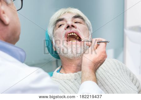 Old man at the stomatologist. Dentist is examining patient.