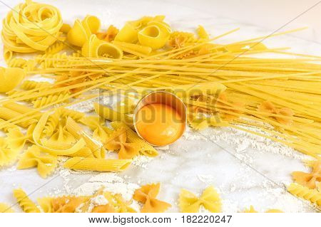 Various types of pasta on a white marble table, with flour and an egg