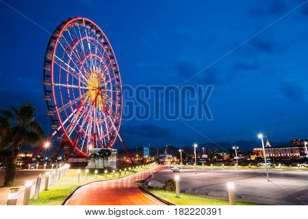 Batumi, Adjara, Georgia - May 26, 2016: Ferris Wheel At Promenade In Miracle Park, Amusement City Park On Blue Evening Sky Background. Blue Hour At Evening Or Night Time