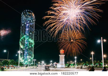 Batumi, Adjara, Georgia - May 26, 2016: Festive Salute During Celebration Of Georgia's Independence Day Over Illuminated Alphabet Tower And Pitsunda Lighthouse At Promenade Near Miracle Park On Night Sky Background