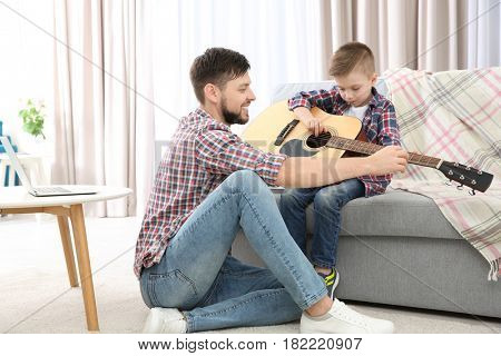 Father teaching his son to play guitar at home