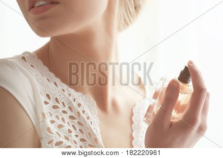 Beautiful young woman with bottle of perfume at home, closeup